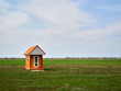 Alone small, orange, wooden house with white door, round window in green field and blue sky with clouds