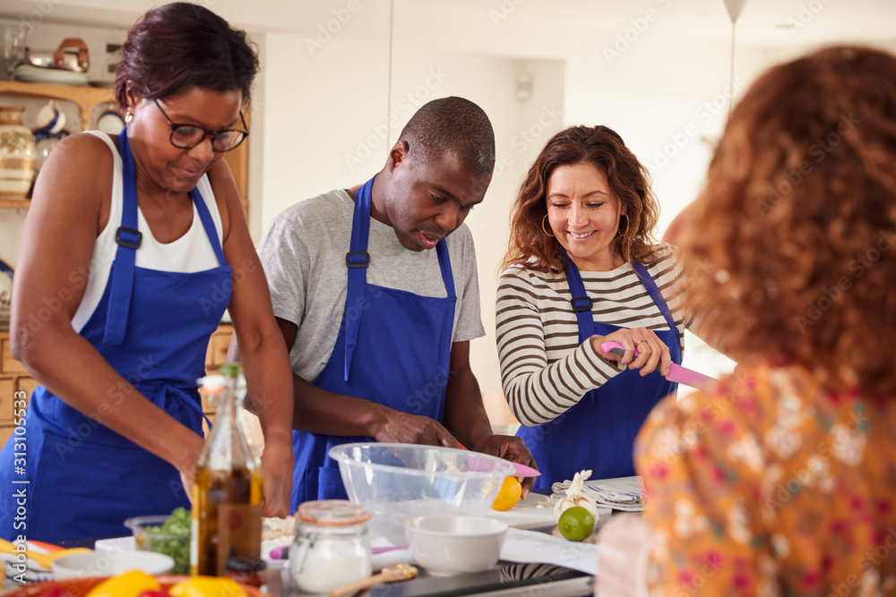 Fototapeta Male And Female Adult Students With Teacher Preparing Ingredients For Dish In Kitchen Cookery Class