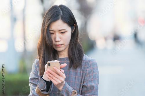 Obraz na plátně  スマートフォンを使う女性