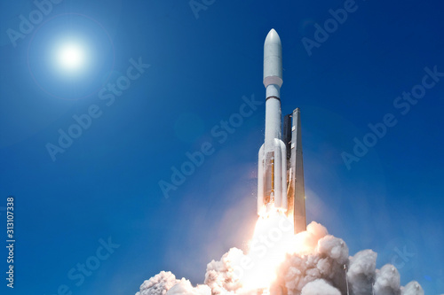 Fotografia Take off space rocket on a background of blue sky and sun