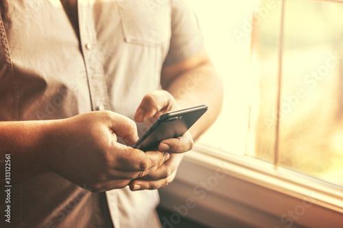 Fotografie, Tablou  Jeune homme utilisant un téléphone portable en intérieur