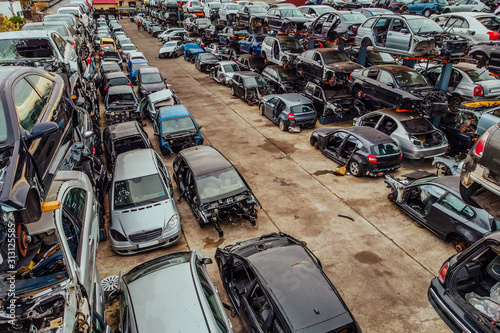 Damaged cars waiting in a scrapyard to be recycled or used for spare parts Fotobehang