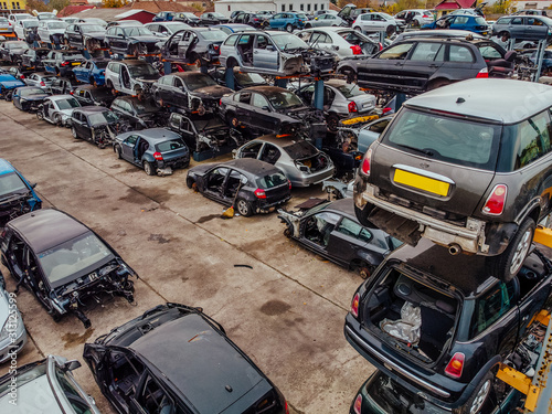 Damaged cars waiting in a scrapyard to be recycled or used for spare parts Wallpaper Mural