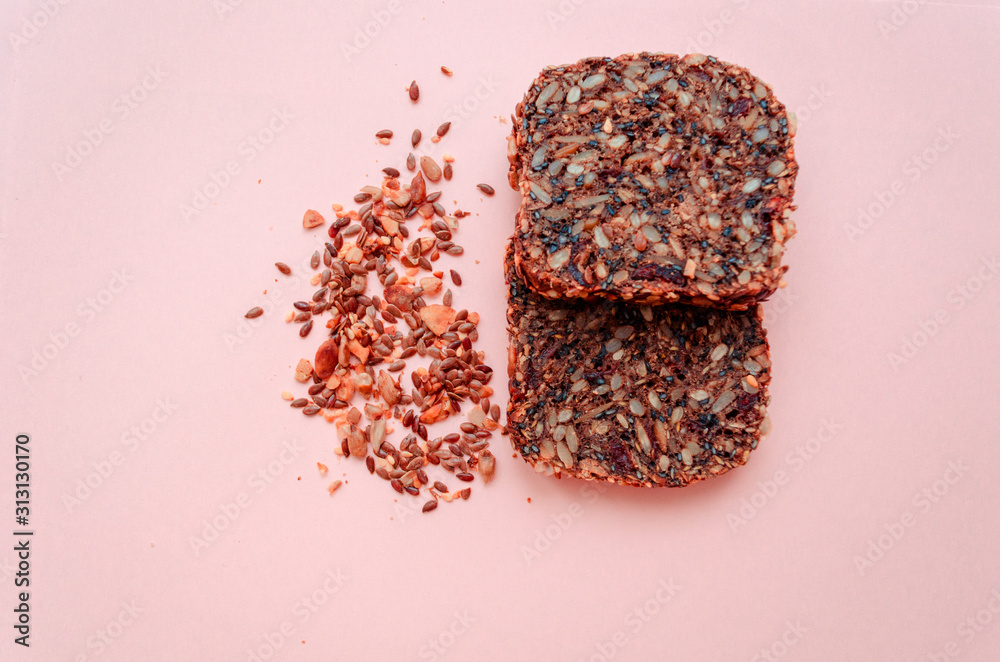 Fototapeta Sliced whole grain bread rye with seeds flax, sunflower, pumpkin and sesame.Healthy food, eco-friendly natural products. Fresh bread on a pink background.