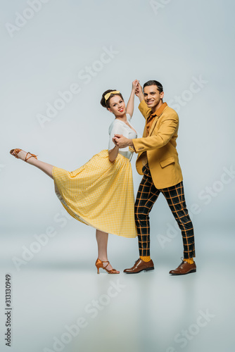 Платно stylish dancers holding hands while dancing boogie-woogie on grey background