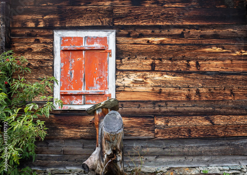 Closed window with vintage orange shutters on an old Swiss farm house