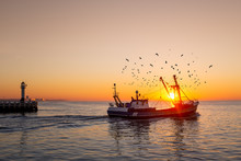 Fishing Boat In Front Of The Old Wooden Pier Of Nieuwpoort (Belgium) At Sunset