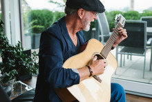 Senior Man Playing Guitar At H...