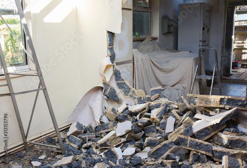 Fototapeta Indoor renovation project, demolition of the wall between two rooms, damaged blo
