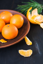 Fresh Whole And Peeled Tangerines Lie On An Old Clay Plate On A Dark Background