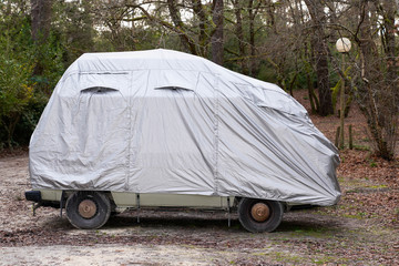 rv camper van car covered with grey protective cover by townhouse for wet weather in parking lot town