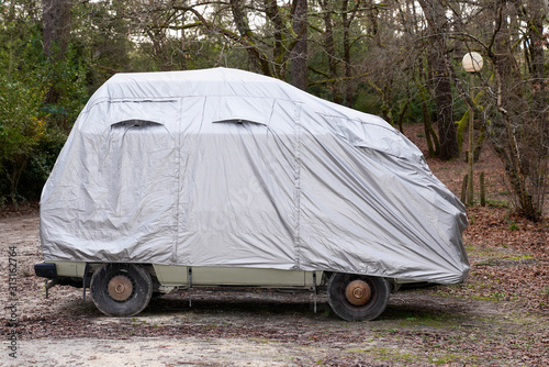 obraz PCV rv camper van car covered with grey protective cover by townhouse for wet weather in parking lot town