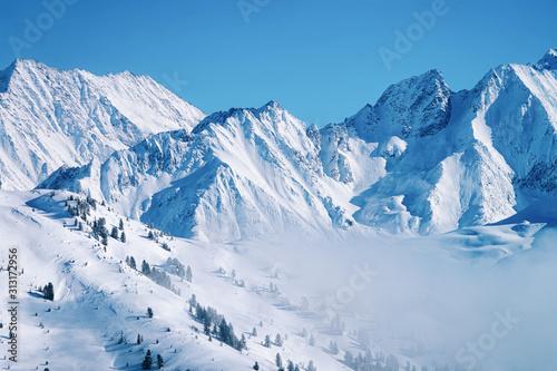 Photo Landscape in Zillertal Arena ski resort in clouds in Tyrol at Mayrhofen in Austria in winter Alps