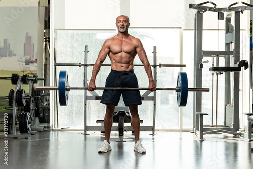 A strong muscular shirtless mature older bodybuilding athlete with balding gray Wallpaper Mural