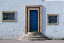 White Facade With Blue Door In...