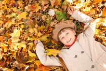 Cute Little Girl Lying On Leaves In Autumn Park