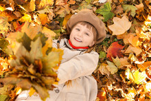 Cute Little Girl Lying On Leaves In Autumn Park