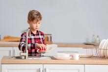Little Boy Washing Dishes In K...