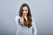Attractive caucasian brunette woman in sweater spread hand for greeting isolated on gray background in studio. People emotions, lifestyle concept.