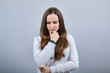 Serious caucasian brunette woman in sweater keeping finger on chin, thinking isolated on gray background in studio. People emotions, lifestyle concept.