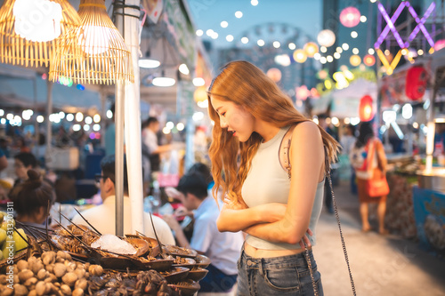 Fototapeta Traveler Asian blogger women travel in Bangkok, Thailand, beautiful female using .Travel vacation at night in the city concept, Young happy traveler asian woman  and backpack walking obraz