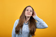 Pleasant caucasian lady wearing fashion shirt isolated on orange background in studio keeping palm near ear, listening. People emotions, lifestyle concept.