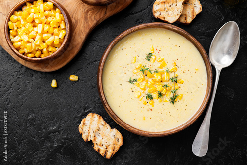 Fototapeta Delicious creamy sweetcorn soup served with toast and corn grains. obraz