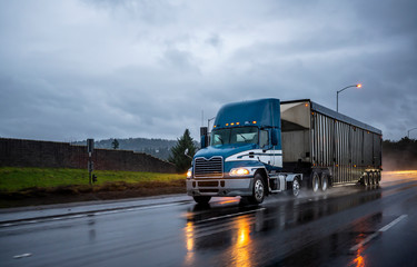 Big rig bonnet blue semi truck transporting cargo in covered bulk semi trailer running on the wet glossy road with raining weather evening