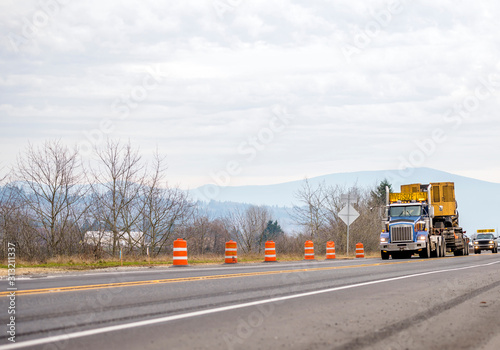 Photo Big rig powerful semi truck with oversized load on the heavy duty semi trailer r