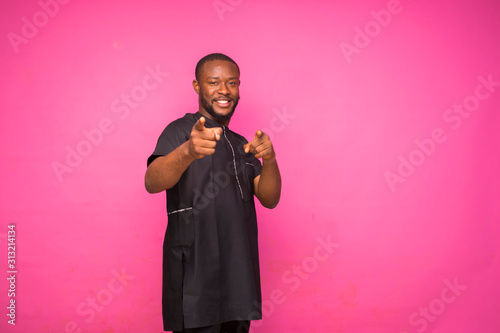 Young African man wearing and black native attire pointing at something in front Wallpaper Mural