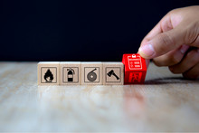 Close-up Hand Choose A Red Wooden Toy Blocks With Insurance Policy Icon For Fire Safety Protection Concepts.