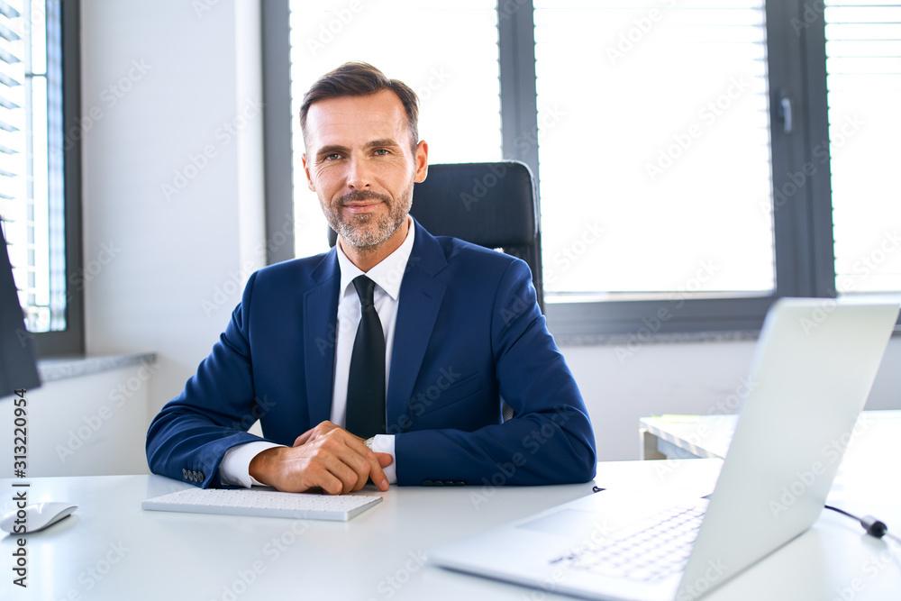 Obraz Smiling mature businessman sitting at office desk looking at camera fototapeta, plakat