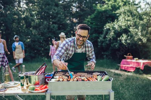 Obraz na płótnie Handsome male preparing barbecue outdoors for friends