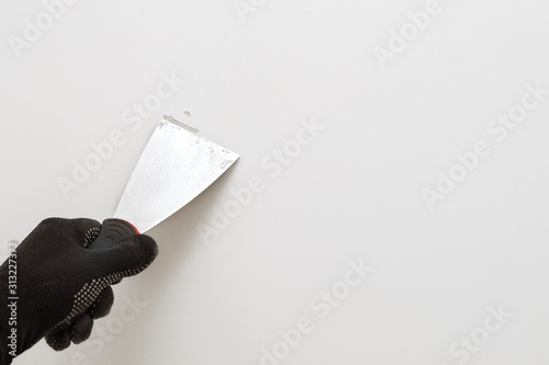 Fototapeta Removing old paint from the wall with a metal spatula. Light background. Working tool, spatula in hand in black gloves against the background of a white wall, work plasterer. Copy space. obraz na płótnie