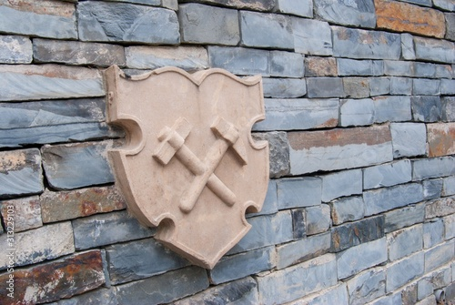 stone blazon with two miner hammers on the wall made from slate bricks Canvas Print