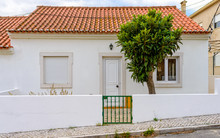 A Small White House With Red Tiles Somewhere In The South Of Portugal