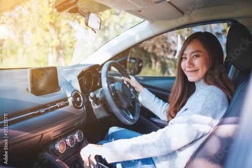 Cuadros en Lienzo  Closeup image a female driver shifting automatic gear stick while driving car
