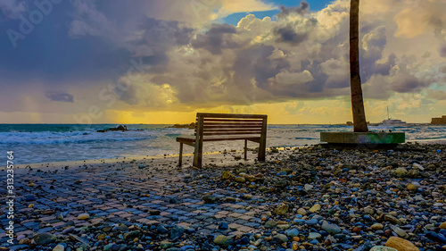 A bench on the coast of the embankment with a stones washed ashore after storm in the city of Paphos Canvas Print