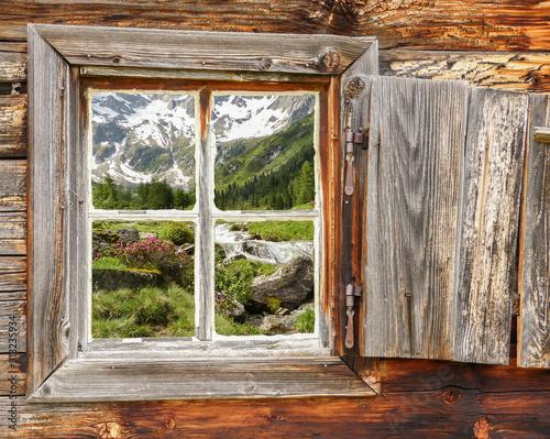 Photo Berglandschaft mit Wildbach und Gletscher gesehen durch ein Holzfenster im Zille