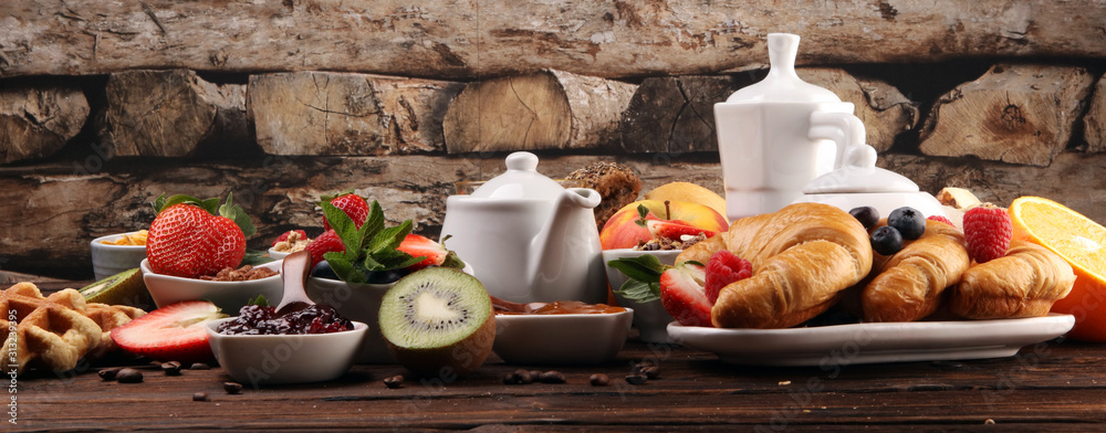 Fototapeta Breakfast served with coffee, orange juice, croissants, cereals and fruits. Balanced diet. Continental breakfast with granola and fruits