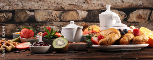 Fototapeta Breakfast served with coffee, orange juice, croissants, cereals and fruits. Balanced diet. Continental breakfast with granola and fruits obraz