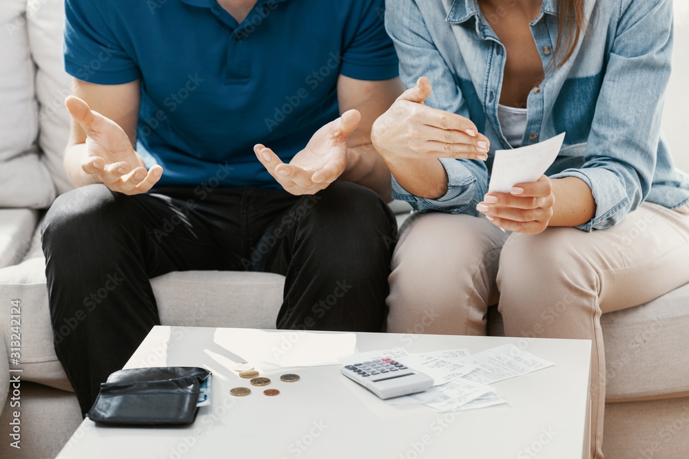 Fototapeta Young anonymous married couple sitting in their living room calculating how many money their have got to pay bills