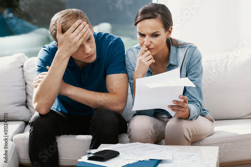 Fotografía  Stressed married couple looking frustrated, having no money to pay off their deb