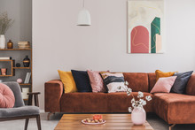 Real Photo Of A Cozy, Brown Corner Sofa With Decorative Cushions Standing In A Bright Living Room Interior With An Abstract Painting