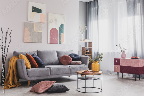 Fototapeta Real photo of abstract paintings hanging on white wall above a gray sofa in a living room interior with big windows obraz