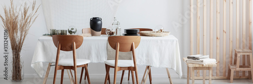 Obraz Wooden chairs and long table in living room - fototapety do salonu