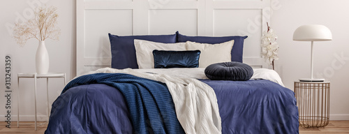 Fotomural Stylish white lamp on trendy bedside table in classy navy bedroom interior