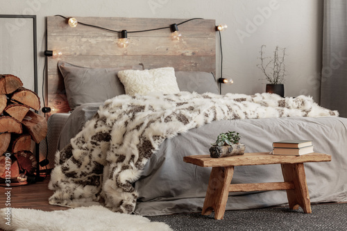 Obraz Wooden bench in the foot of the bed with grey bedding and cozy blanket - fototapety do salonu