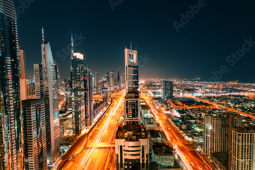 Photo Night view of the spectacular landscape of Dubai with high-rises and skyscrapers at the Sheikh Zayed highway