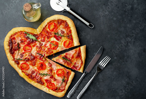 heart-shaped pizza for Valentine's day on a stone background. Valentine's Day gala dinner for two with copy space for your text.